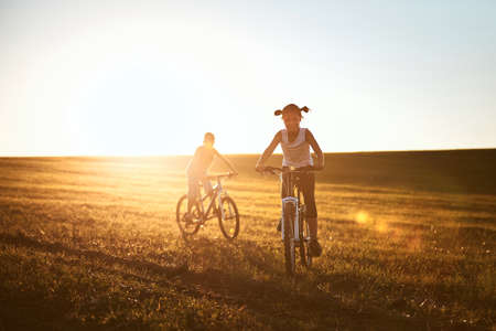 Girl and boy enjoying bike ride on meadow. Summertime trip in  countryside at sunset. Banco de Imagens