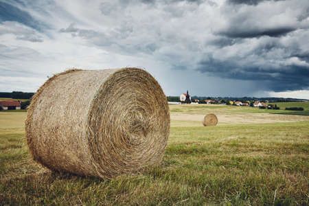 Straw bales stacked on field against landscape with village. Themes rural, agriculture, and weather. Banco de Imagens