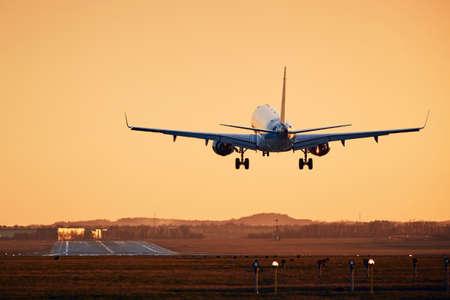 Airplane landing on runway. Traffic at airport at golden sunset. Stock Photo