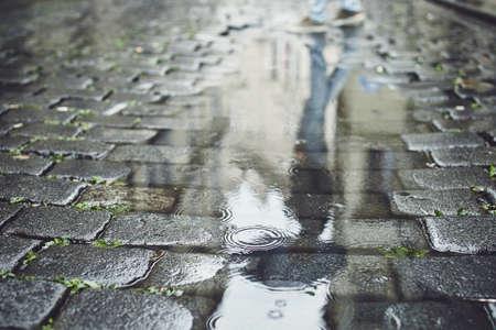 Reflexión en charco. Hombre con paraguas caminando por la calle adoquinada bajo la lluvia. Praga, República Checa.