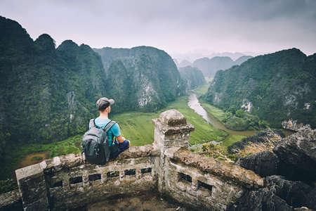 Traveler in Vietnam. Pensive Young man with backpack sitting on peak Mua Cave. Ninh Binh province, Vietnam. Stock Photo