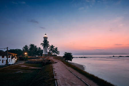 Beautiful historical lighthouse in fort in Galle. Old town in Sri Lanka at colorful sunrise.