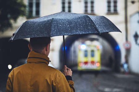 Man with umbrella looking at leaving ambulance car of emergency medical service in rainy day. Prague, Czech Republic Banco de Imagens