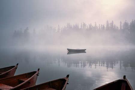 Boats on mountain lake in mysterious fog. Strbske pleso in High Tatras, Slovakia. 版權商用圖片