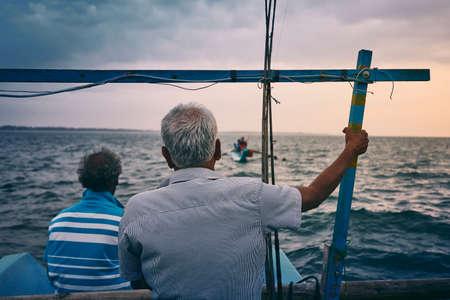 Hard work on sea. Two fishermen on fishing boat at sunrise near coastline of Sri Lanka.