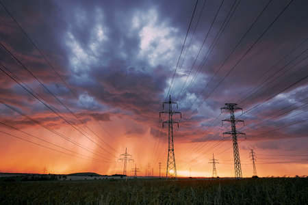 Extreme weather. Electricity pylons with power lines against stunning storm at sunset.