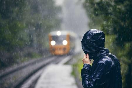 Hombre en chaqueta empapada de pie en el andén de la estación de tren contra el tren bajo una intensa lluvia.