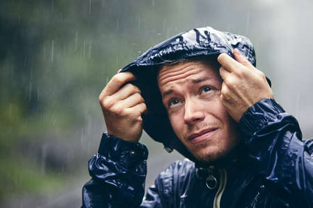 Trip in bad weather. Portrait of young man in drenched jacket in heavy rain. Banco de Imagens