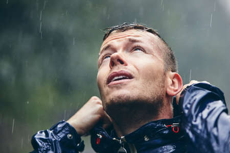 Trip in bad weather. Portrait of young man in drenched jacket in heavy rain. Stok Fotoğraf