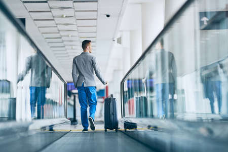 Well dressed young man travel by airplane. Businessman with luggage walking on travelator at airport.