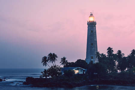 Illuminated lighthouse in the middle of palm trees. South coast of Sri Lanka at sunset.