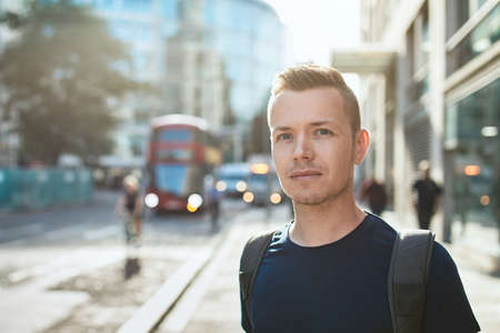 Portrait of young man against city street with bus of public transportation. London, United Kingdom