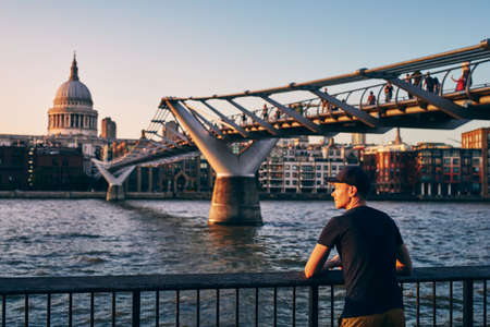 Young man relaxing on riverside against urban skyline. Contemplation at sunset. London, United Kingdom. Banco de Imagens