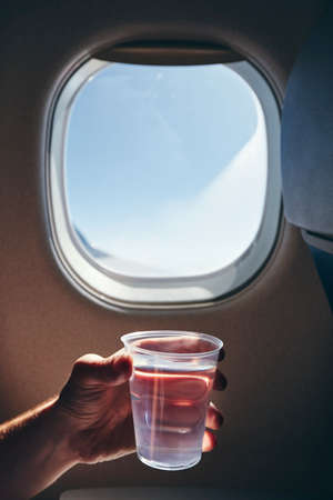 Refreshment during flight. Human hand holding cup of drinking water against airplane window. Banco de Imagens