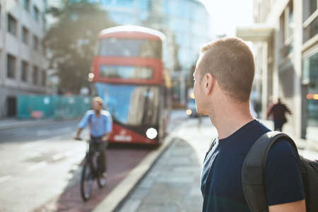 Young man waiting for bus of public transportation. City life in London, United Kingdom Reklamní fotografie