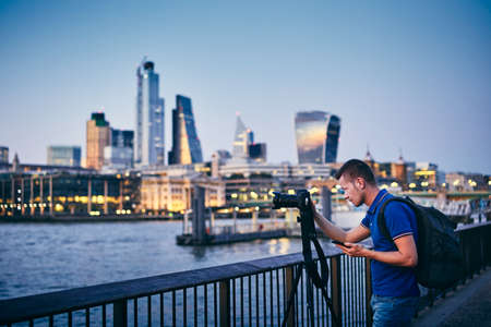 Young man photographing with tripod on embankment against urban skyline. Photographer holding smart phone with app. City life in London, United Kingdom.