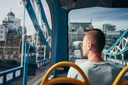 Young man looking through window from double decker bus. City life in London, United Kingdom. Banco de Imagens