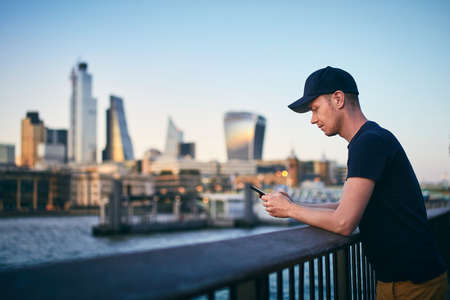 Side view of young man while using smart phone against London skyline at dusk.