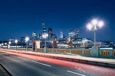 Light trail of car on bridge against illuminated urban skyline. London, United Kingdom