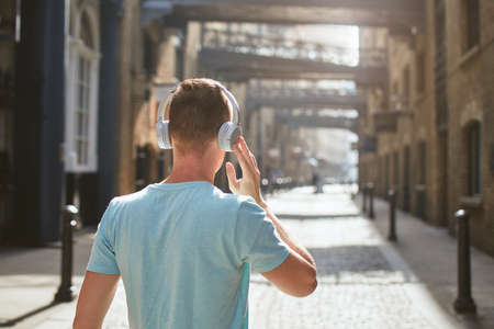 Young man with headphones listening music against old city street at morning light. London, United Kingdom.