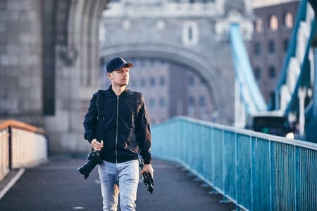 Photographer looking away while carrying camera and tripod against Tower Bridge. London, United Kingdom.