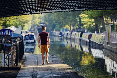 Young man walking on waterfront of Regents canal with boats. Little Venice in London, United Kingdom. 写真素材
