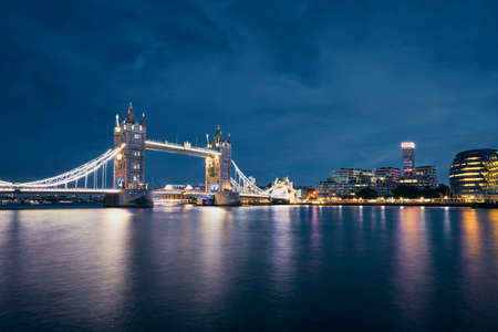 Night view of Tower Bridge against cityscape with City Hall at night. London, United Kingdom.