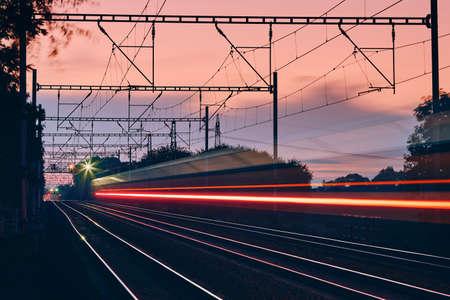 Railway at dawn. Light trails of passenger train on modern railroad track. Banco de Imagens