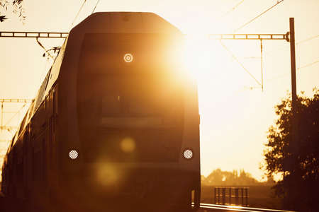 Railway at sunrise. Front view of passenger train against sun.