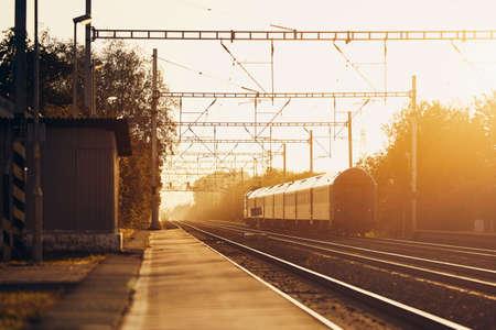 Railway at sunrise. Passenger train leaving from railroad station. Banco de Imagens