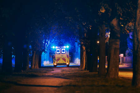 Rescue in dark city alley. Rear view of ambulance of emergency medical service against illuminated trees from blue flasher.