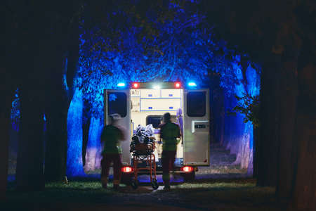 Doctor and paramedic of emergency medical service rescuing old patient. Themes health care, rescue and hope. Banco de Imagens
