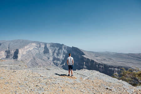 Young tourist standing on the edge of cliff at sunrise. Jebel Akhdar, Grand Canyon of Oman.