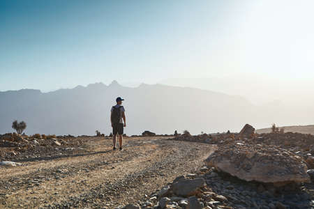 Young tourist with backpack on mountain road at sunset. Jebel Akhdar, Oman.