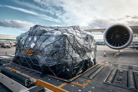 Preparación antes del vuelo. Carga de contenedor de carga contra avión. Foto de archivo
