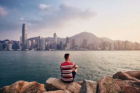 Young man sitting on stones against Hong Kong cityscape with skyscrapers at colorful sunset. Stock Photo