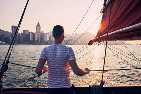 Traveler on traditional junk boat crossing Victoria Harbor against Hong Kong cityscape with skyscrapers at golden sunset.