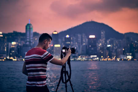 Young photographer (traveler) with tripod photographing urban skyline at sunset, Hong Kong. Stock Photo