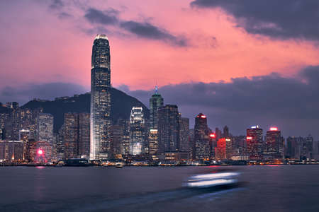 Victoria Harbour and urban skyline with illuminated skyscrapers at dusk, Hong Kong.
