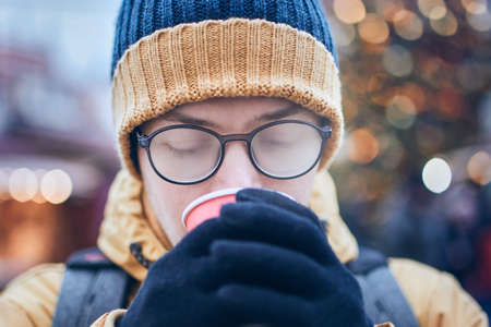 Young man with foggy up eyeglasses drinking hot wine. Christmas market in Tallinn, Estonia.