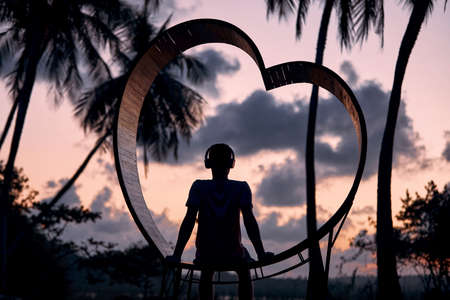 Relaxation in tropical paradise. Young man with headphones sitting in wooden heart and listening music against palm trees at beautiful sunset.