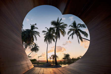 View to landscape throught wooden heart. Palm tree near lagoon at sunset in Sri Lanka.