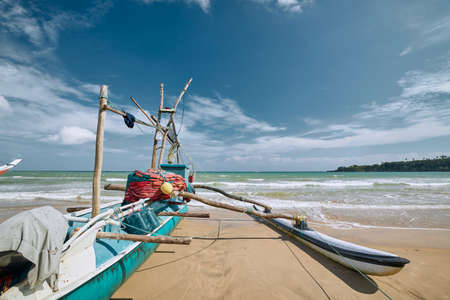 Traditional fishing boat on sand beach at sunny day, Sri Lanka 写真素材
