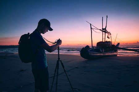 Silhouette of young photographer (traveler) with tripod on beach against fishing boat and sea. Beautiful sunrise in Sri Lanka.