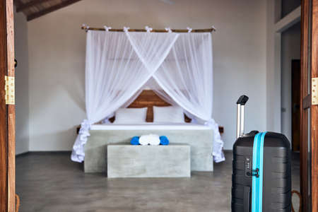 Luxury accommodation in tropical destination. Suitcase in door of bungalow against bed with mosquito net.