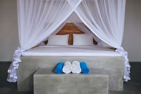 Luxury accommodation in tropical destination. Double bed with mosquito net in modern bungalow. 写真素材