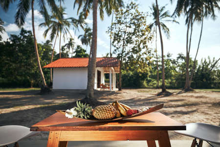 Luxury accommodation in tropical destination. Fruit in bowl on wooden table against bungalow under coconut palm trees.