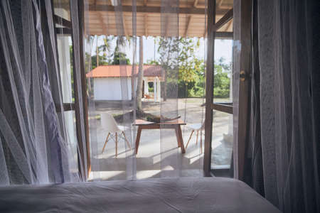 Luxury accommodation in tropical destination. Selective focus on mosquito net in bedroom of bungalow with view to garden.