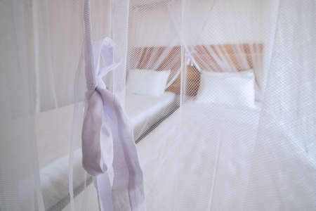 Luxury accommodation in tropical destination. Selective focus on mosquito net in bedroom of bungalow.