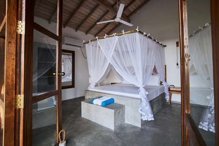 Luxury accommodation in tropical destination. Door of bungalow against large bed with mosquito net. 写真素材
